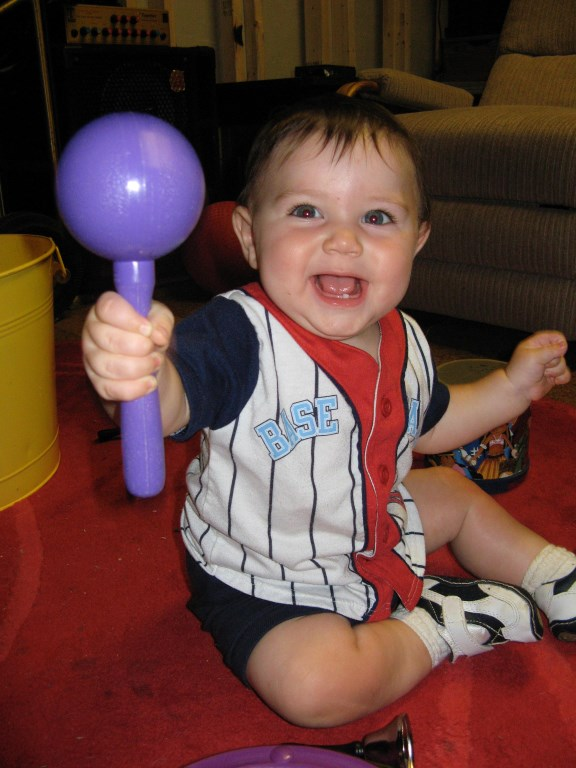 Child holding up a single purple maraca