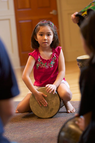 Older Rhythm Kid striking the djembe